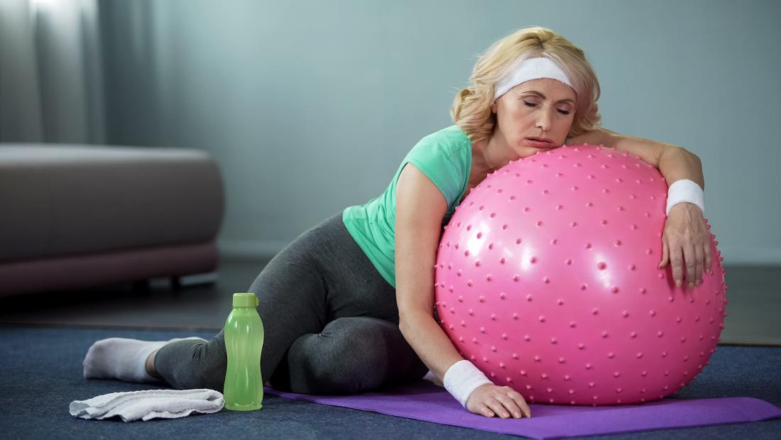 exhausted woman lying on exercise ball