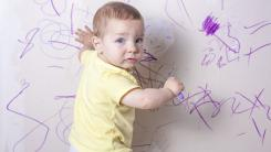 baby drawing with crayon on wall