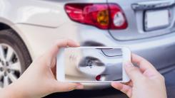 person using smartphone to photograph damage to car