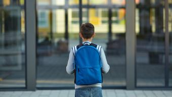 child with backpack on facing front of school