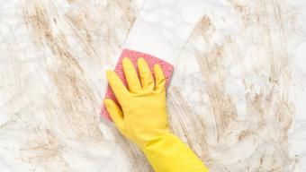 gloved hand cleaning marble countertop with sponge