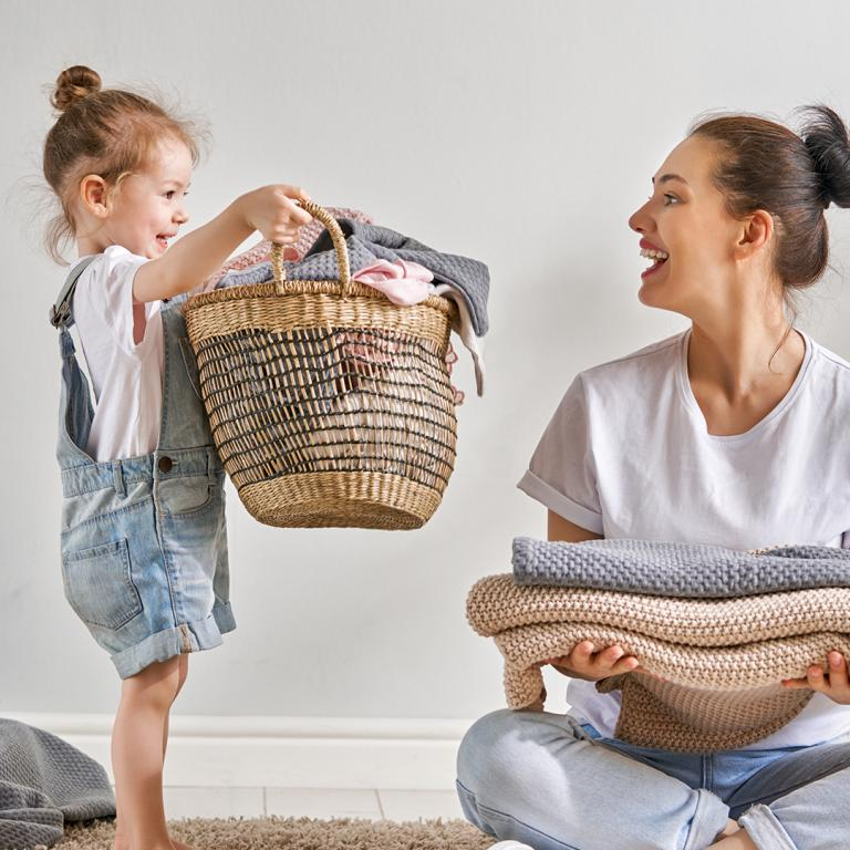 Young Girl With Mom Holding Laundry Basket