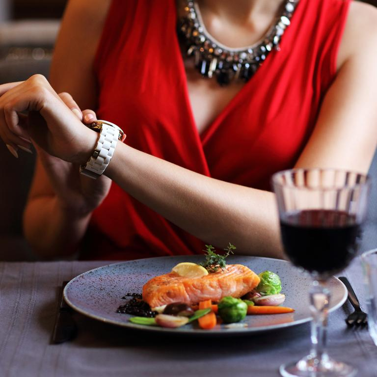 woman checking her watch at dinner party