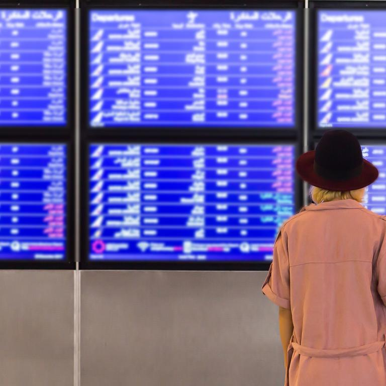 Woman looking at airport departures/arrivals board