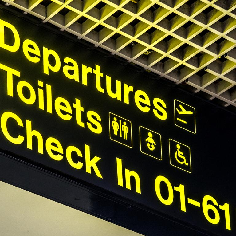 Airport sign with arrows directing to departures, toilets and check in