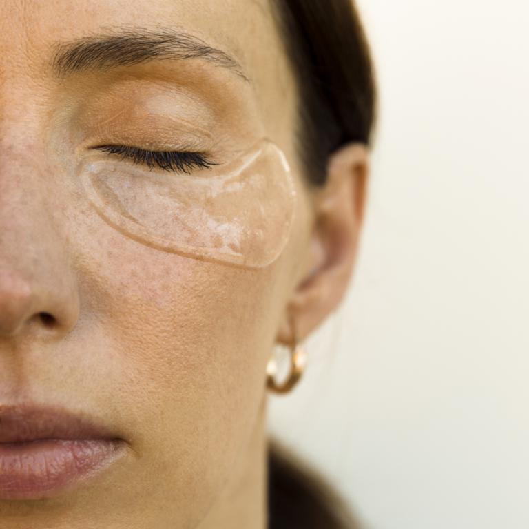 Woman with skincare treatment under eyes
