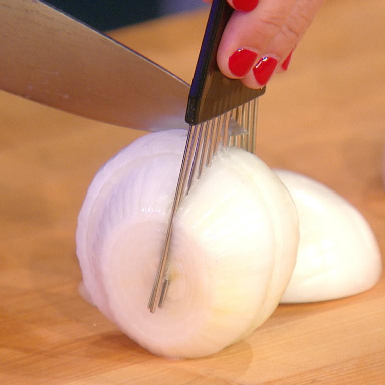 chopping an onion using a hair pick to hold it steady