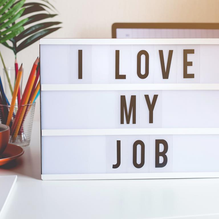 "sign on desk that says ""I love my job"""