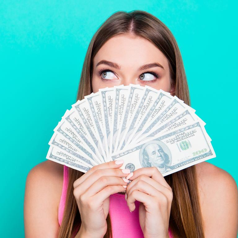 woman holding money in front of her face