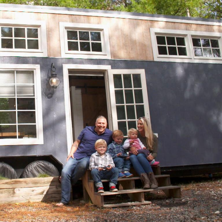 family of 5 in front of tiny house