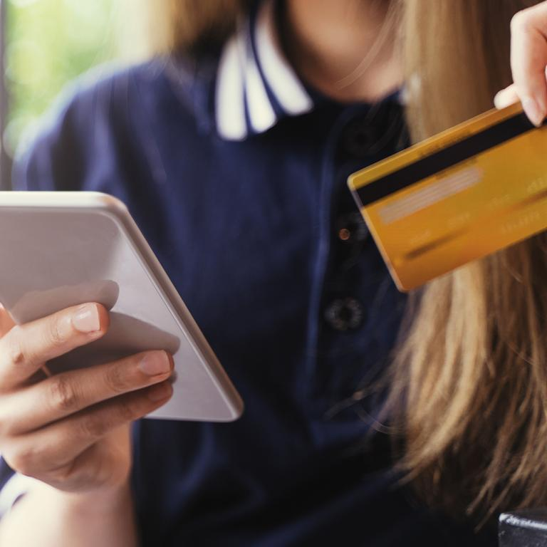 woman holding her debit card and looking at her phone