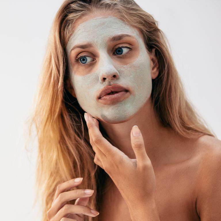 woman looking in mirror with clay face mask on