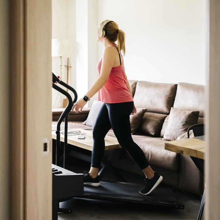 Woman Working Out At Home On Treadmill