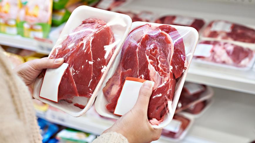 comparing prices of meat at grocery store
