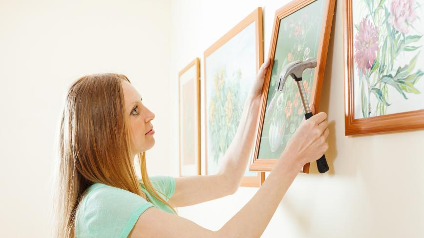woman hanging framed art on wall