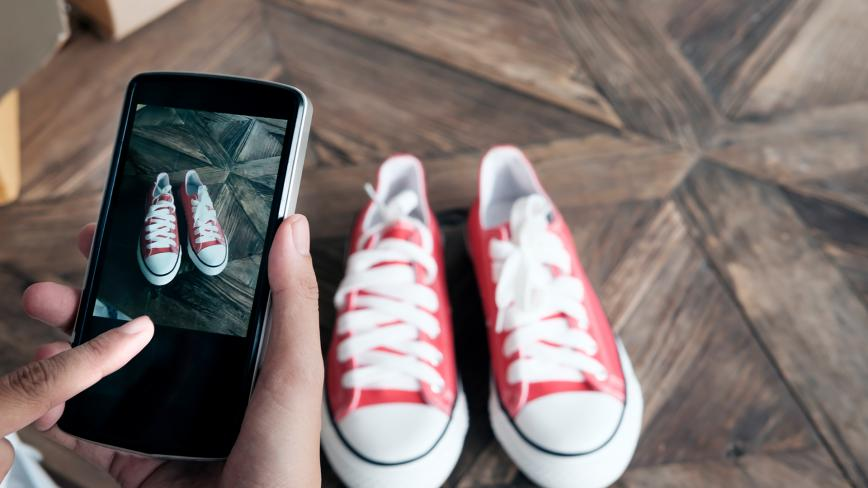 hands using a smartphone to photograph a pair of shoes