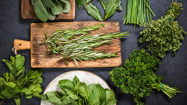 Various fresh herbs laid on and around a cutting board